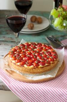 Torta, torta ou cheesecake com queijo cottage e tomate, servido com vinho tinto em um fundo de madeira.
