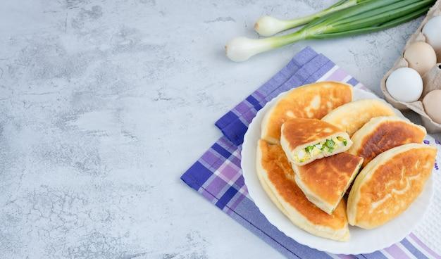 Tortas caseiras com cebolinha e ovos, dispostas em um prato redondo branco com penas de cebolinha. vista de cima.