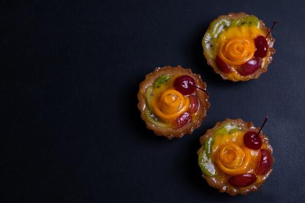 Tortas caseiras de frutas com kiwi laranja e cereja em preto