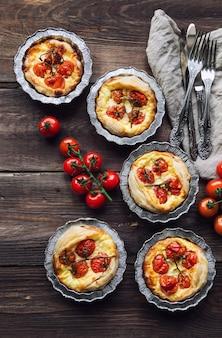 Tortas caseiras frescas com tomate cereja e queijo de cabra em fundo de madeira rústico. vista do topo.