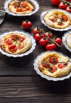 Tortas caseiras frescas com tomate cereja e queijo de cabra em fundo de madeira rústico.