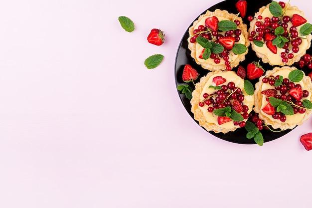 Tortas com morangos, groselha e chantilly, decoradas com folhas de hortelã