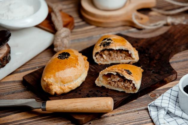 Tortas de carne de massa de pão em uma placa de madeira