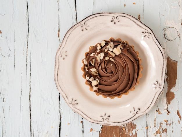 Tortas de chocolate servidas com nozes de amêndoa na superfície de madeira branca gasto