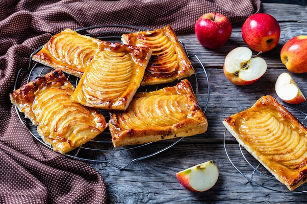 Tortas de massa folhada de maçã com caramelo em um suporte de metal em uma mesa rústica de madeira com um pano marrom, closeup