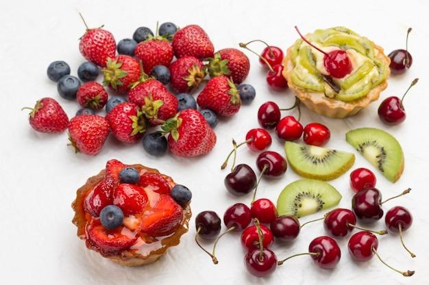Tortas decoradas com frutas frescas. morango e mirtilos, kiwi e cereja vermelha na superfície branca. espaço da cópia plana lay.