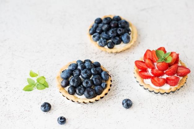 Tortas doces com frutas vermelhas frescas no verão, framboesas, morangos e mirtilos
