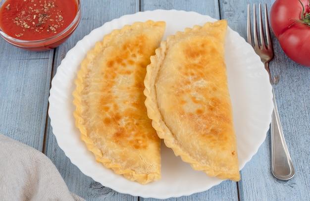 Tortas fritas com carne - chebureks em um prato, uma tigela com molho de tomate