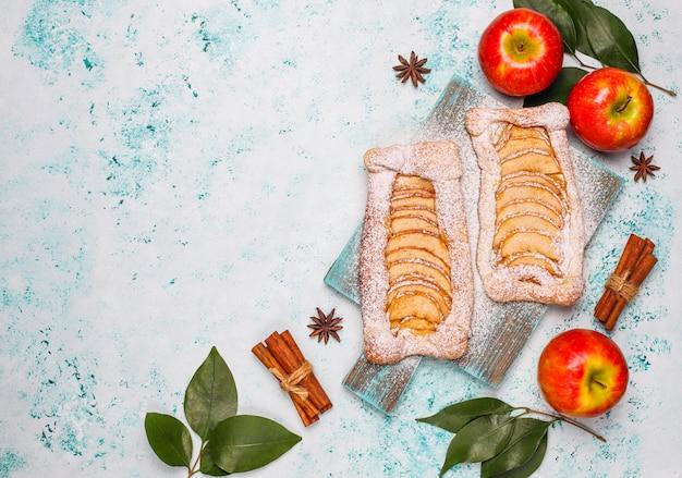 Tortas orgânicas caseiras de massa folhada de maçã com maçãs prontas para comer