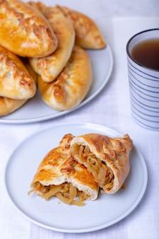 Tortas pirozhki com repolho e xícara de chá