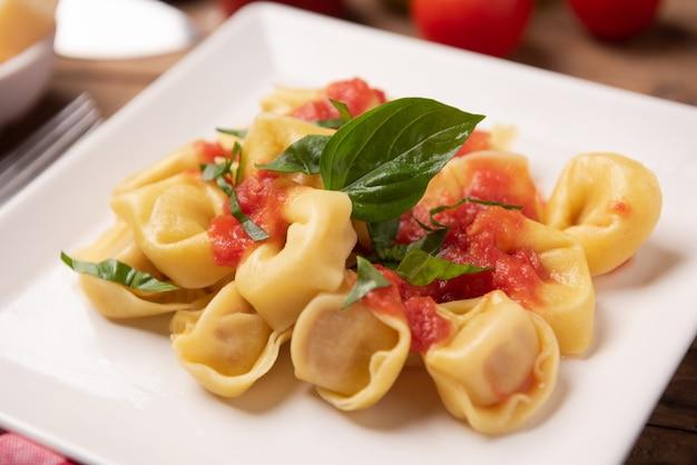 Tortellini com molho de tomate no prato close up