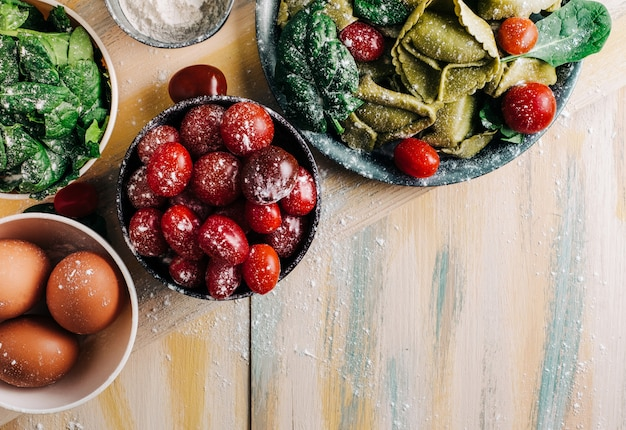 Tortellini de espinafre em uma mesa de madeira velha, cercada por ingredientes frescos: tomate, farinha, espinafre, ovos. comida vegana. copyspace