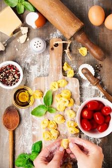 Tortellini de massa italiana crua na placa de madeira