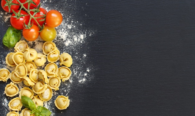Tortellini fresco com manjericão e tomate em um quadro escuro com vista superior
