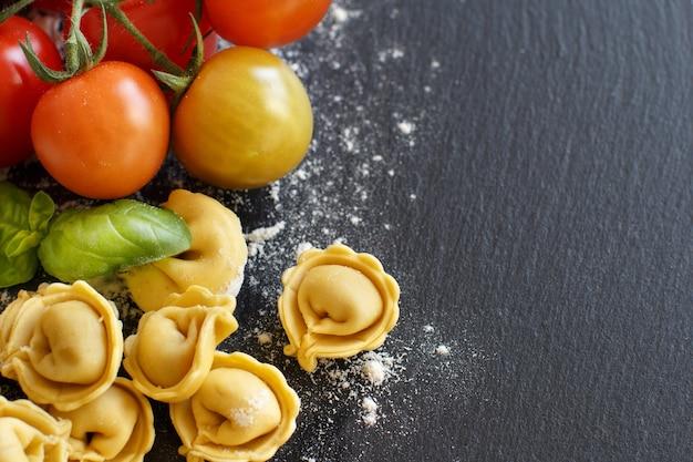 Tortellini italiano cru caseiro com tomate fresco e manjericão em uma superfície escura
