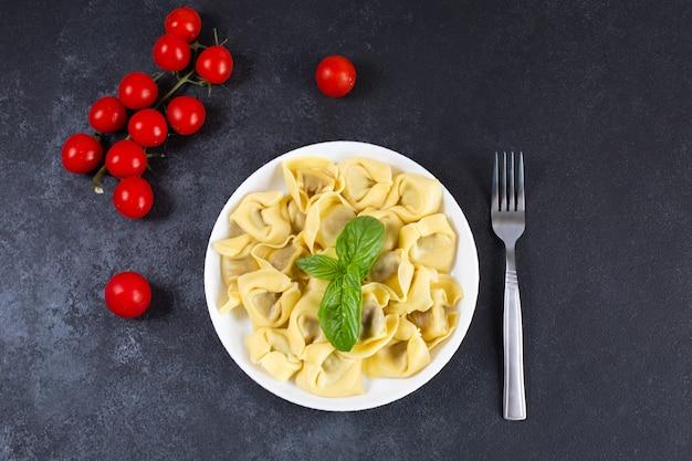 Tortelloni italiano caseiro decorado com manjericão fresco em um prato