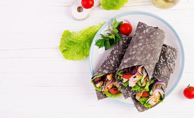 Tortilha com tintas de choco adicionadas com frango e legumes