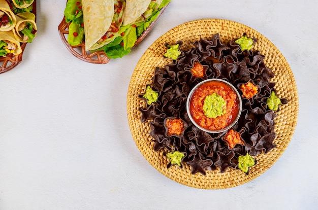 Tortilha de milho azul com salsa e guacamole comida hispânica.