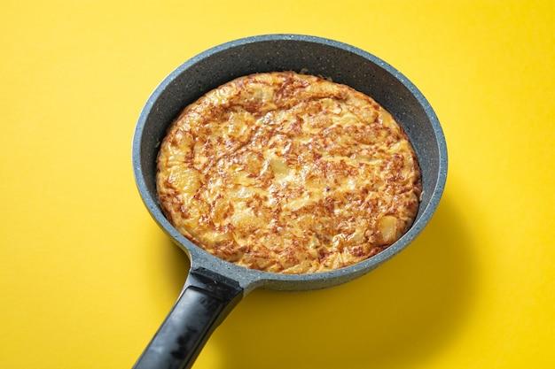 Tortilha de patatas no frigideira no prato espanhol amarelo, típico.