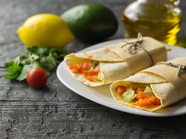 Tortilha de rolo de dois vegetais de farinha de trigo em uma tigela branca e limão e abacate em uma mesa de madeira com ervas