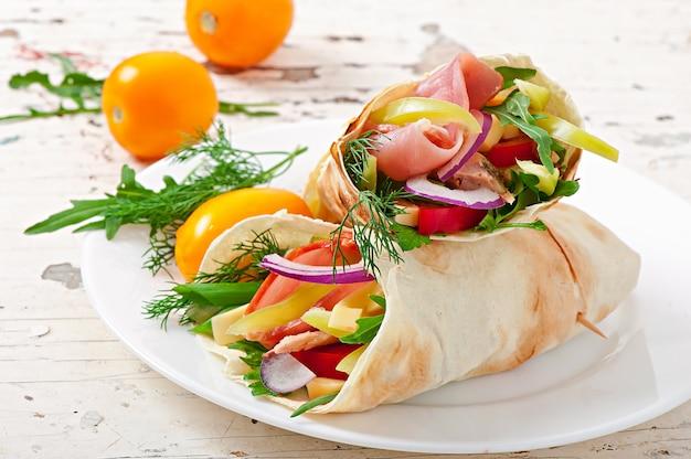 Tortilha fresca envolve com carne e legumes no prato