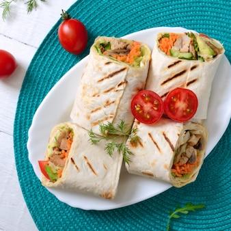 Tortilha fresca envolve com frango, cogumelos e legumes frescos. burrito de frango mexicano. aperitivo saboroso. pratos de pão árabe. conceito de comida saudável