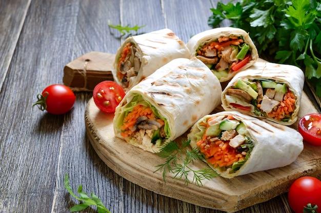 Tortilha fresca envolve com frango, cogumelos e legumes frescos na placa de madeira. burrito de frango mexicano. aperitivo saboroso. pratos de pão árabe. conceito de comida saudável.