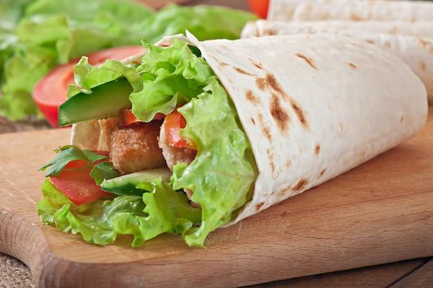 Tortilha fresca envolve com nuggets de frango e legumes no prato