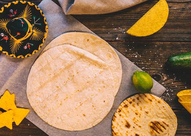 Tortilha mexicana de trigo; saborosos nachos e limões na mesa de madeira com chapéu mexicano