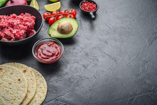 Tortilha mexicana tradicional com uma mistura de ingredientes, milho, carne, vegetais, salsa, molho sobre fundo preto texturizado