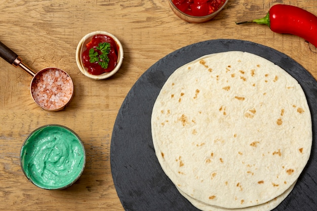 Tortilha perto de molhos, sal rosa e pimenta na mesa