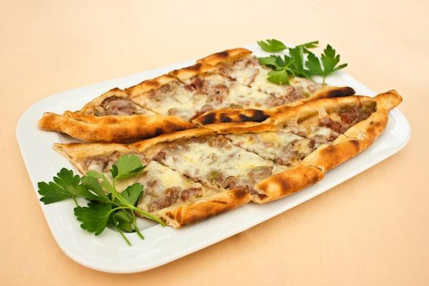 Tortilha turca pita com pedaços de carne, queijo derretido e fatias de legumes