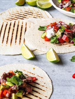 Tortilhas com legumes e fatias de bife. abacate, tomate, cebola roxa e suco de coentro e limão em tortilhas. comida mexicana.