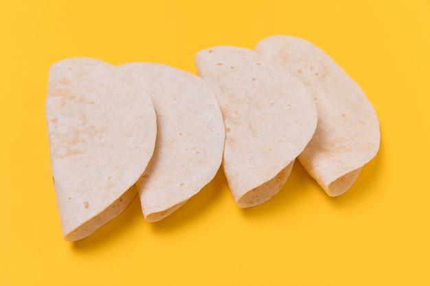 Tortilhas de alto ângulo em fundo amarelo