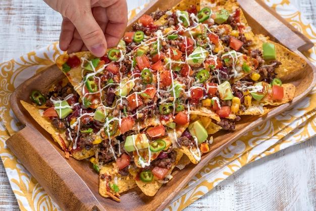 Tortilhas de nacho de milho com queijo, carne, guacamole e molho picante encarnado