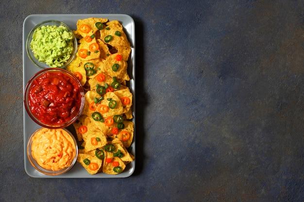 Tortilhas de tortilla de milho amarelo mexicano nachos com jalapeno, guacamole, molho de queijo e salsa