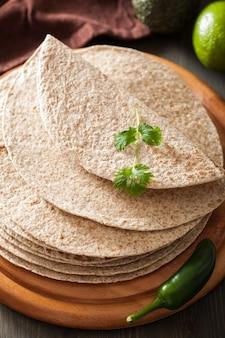 Tortilhas de trigo integral na placa de madeira e legumes