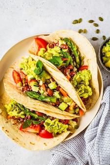 Tortilhas vegan com quinoa, espargos, feijão, legumes e guacamole.