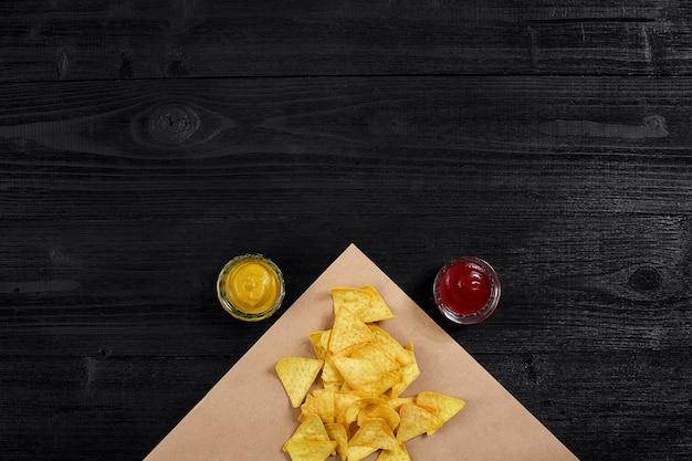 Tortilla chips com mostarda e molho de tomate em vista de mesa de madeira preta