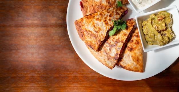 Tortilla de trigo integral grelhada recheada com batata doce e feijão vermelho, queijo quesso vegan servido com molho de guacamole e molho tzaziki.