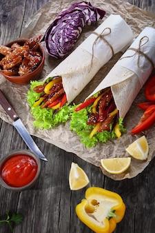 Tortilla enrolada com salada de repolho roxo, tiras de pimentão e frango frito
