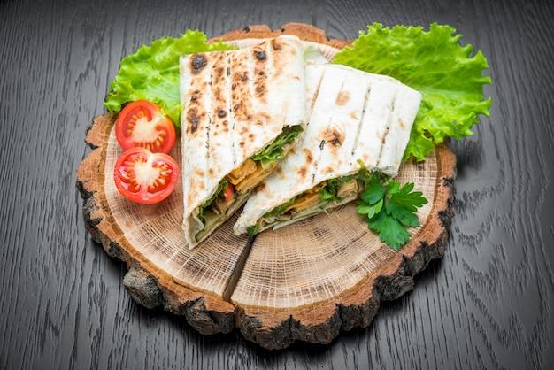 Tortilla envolve com frango grelhado em um fundo de madeira.