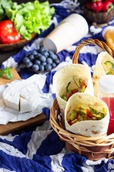 Tortilla envolve frango e legumes assados, sucos, legumes e frutas, baguete e queijo.