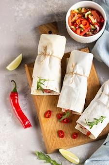 Tortilla envolve sanduíches com legumes na tábua de madeira com salada, limão e pimenta