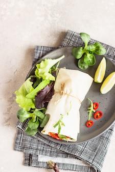 Tortilla envolve sanduíches de salada de legumes servidos com mix de salada, limão e pimenta