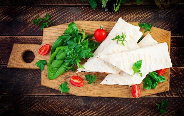 Tortilla grelhada envolve com frango e legumes frescos na placa de madeira. burrito de galinha. comida mexicana. conceito de comida saudável. cozinha mexicana. vista superior, no alto