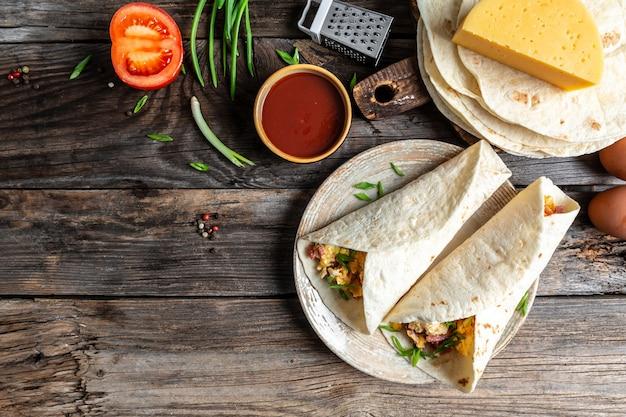 Tortilla mexicana de quesadilla com ovos mexidos, vegetais, presunto e queijo