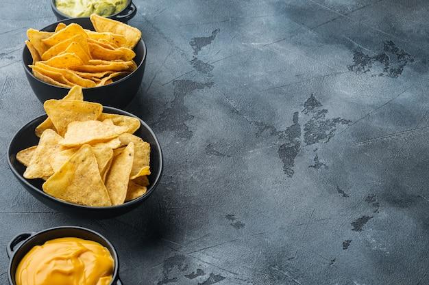 Tortilla nacho com molho de natas servida com molho de guacamole e molho de queijo, em mesa cinza