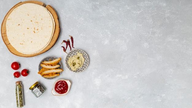 Tortilla redonda com mergulhos ao lado de frango assado
