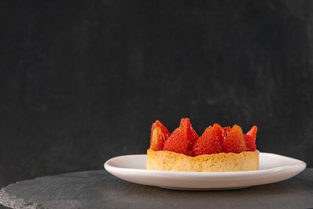 Tortinha com morangos frescos em pires em fundo preto. vista lateral. bolo de frutas. copie o espaço